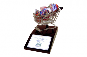 Miniature shopping cart and groceries on a black Lucite base